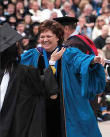 President Pasquerella congratulates a new graduate.