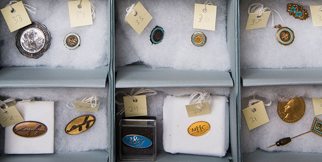 An archival storage box holds the Archives' jewelry and pin collection, including class rings, charms, and other symbolic items.
