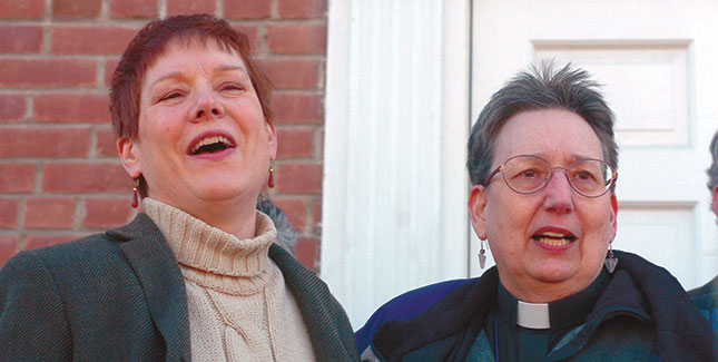 Ministers Dawn Sangrey '93 (left) and Kay Greenleaf lead a crowd of supporters in a hymn in front of New Paltz, NY, courthouse on March 22, 2004. Later, they were arraigned on criminal charges for officiating over same-sex weddings. Photo by Tim Roske, AP