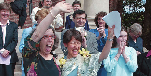 Ellen Wade '70 (right) and Maureen Brodoff wave to cheering well-wishes on the steps of Newton, Mass., City Hall following their May 17, 2004, marriage ceremony. Duaghter Katie Wade-Brodoff stands clapping at far right.