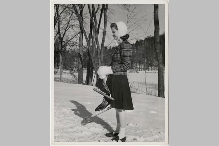 Student standing near the bank of frozen Lower Lake, holding ice skates, 1941.
