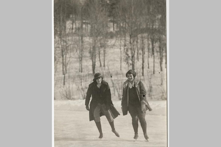 Mary P. Bruyn, class of 1924 and Winifred A. Sanders, class of 1924, skate on Lower Lake with Prospect Hill in the background.