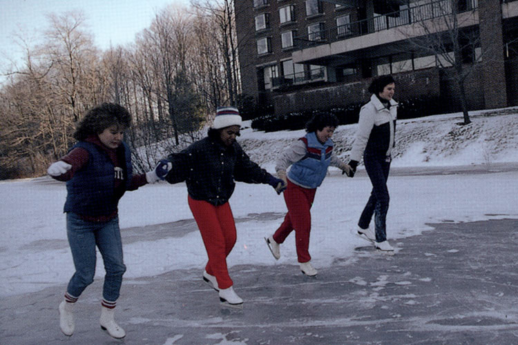 Four students ice skating on Upper Lake, with MacGregor Hall dormitory in the background