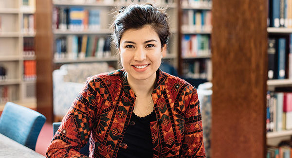 Sajia Darwish '18 smiling while seated in library