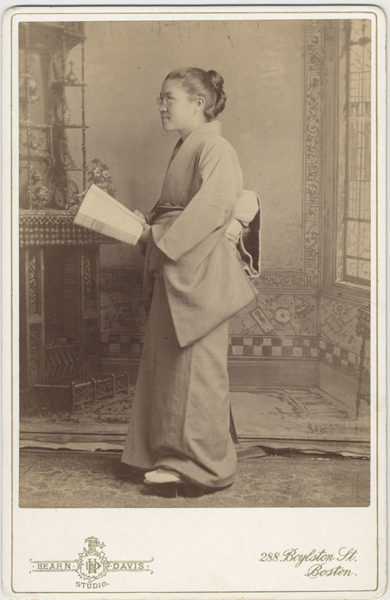 Full-length portrait of Toshi Miyagawa, class of 1893, in Japanese dress, holding book.