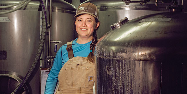 Photo fo Kate Telman in overalls with brewing stills
