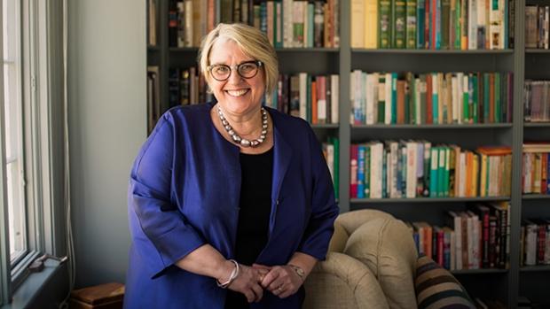 Sonya Stephens in purple jacket stands smiling against a bookshelf