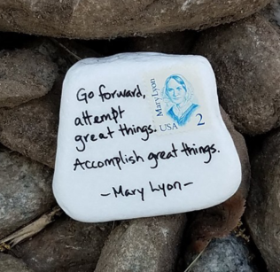 "A rock painted white with a Mary Lyon two cent stamp quotes the founder: ""Go forward, attempt great things. Accomplish great things."""
