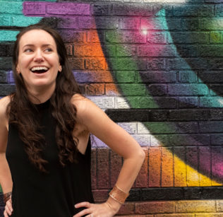 Merli Guerra stands before a colorfully painted brick wall.