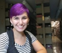 Yaine Neyhard sits in the library, wearing a striped shirt, with short, purple hair.