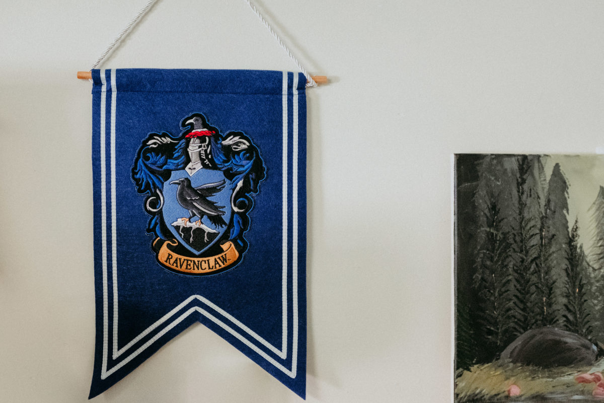 A close-up of a Ravenclaw pennant in a student's room. To the right is part of a painting of a woodland scene.