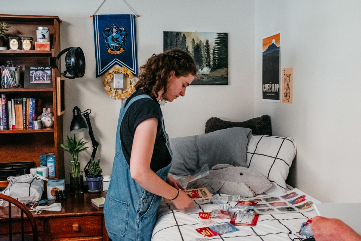 A student considers the packages of command strips on their bed as they decorate their room.