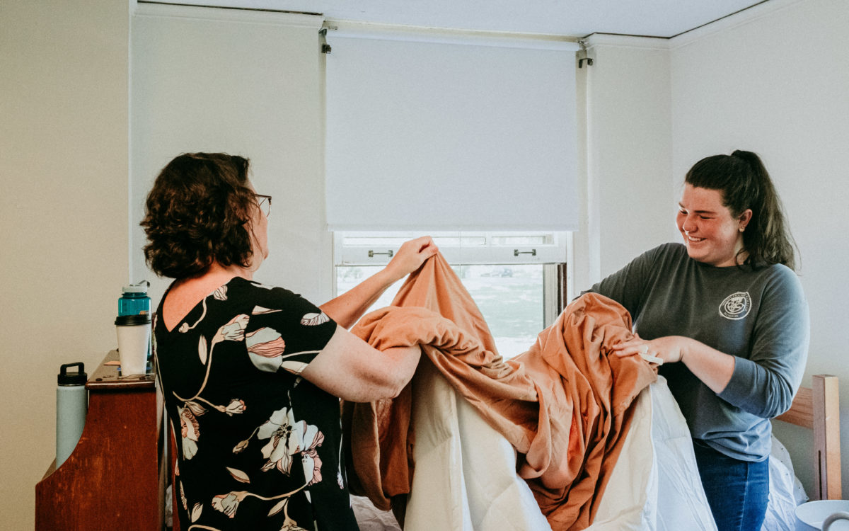 A student and their parent unfolds a set of orange and white bedsheets.