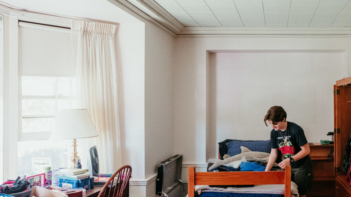 A student leans over their bed as they set up their room in Abbey Hall. Sunlight streams in from the large bay window to the left.