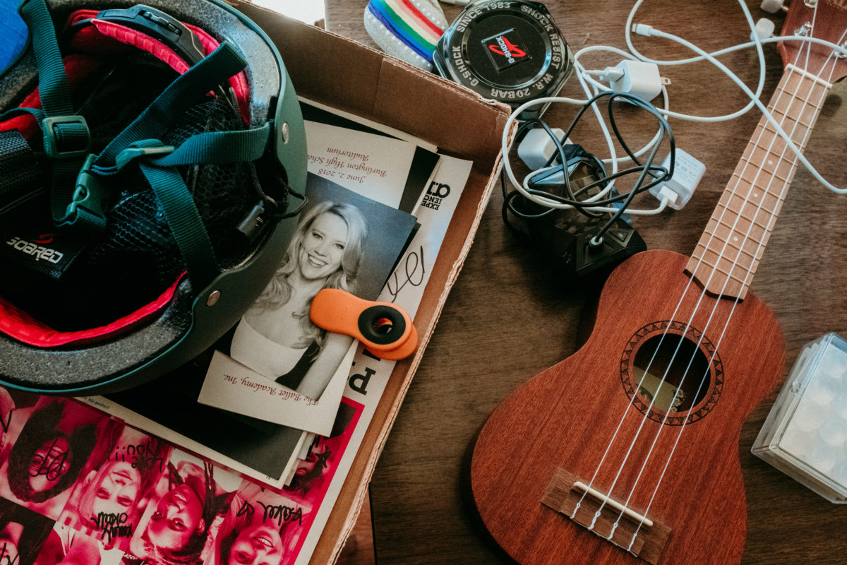 A close-up of a student's items. Most prominent are a ukulele, a helmet and a photo of Kate McKinnon.