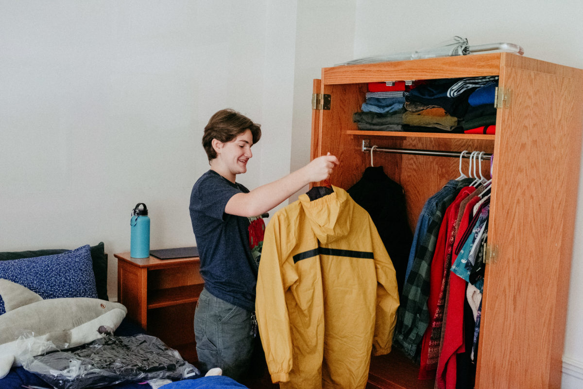 A student hangs up a yellow windbreaker in their armoire.
