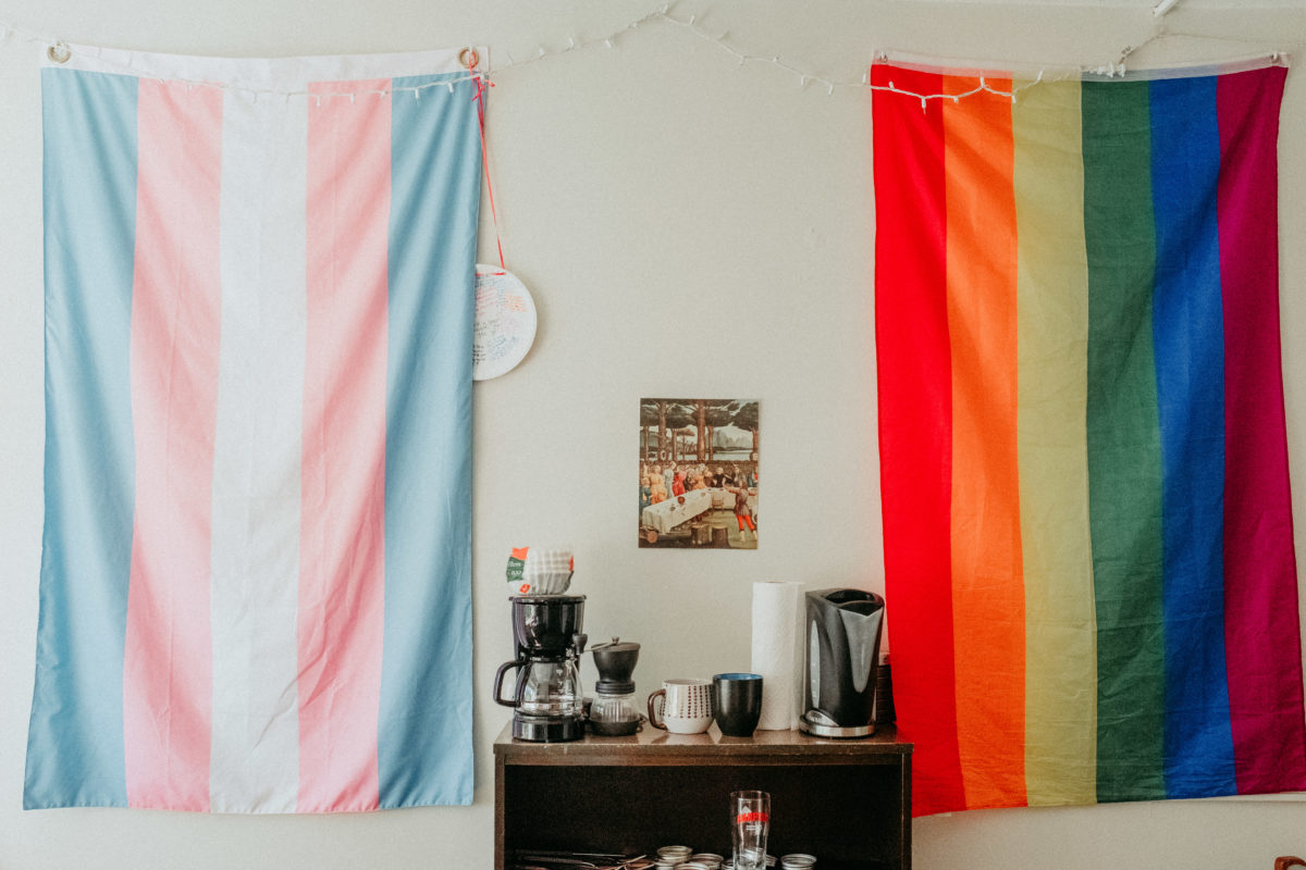 A transgender pride flag and a gay pride flag hang on either side of a bookshelf with a coffeemaker and mugs on top.