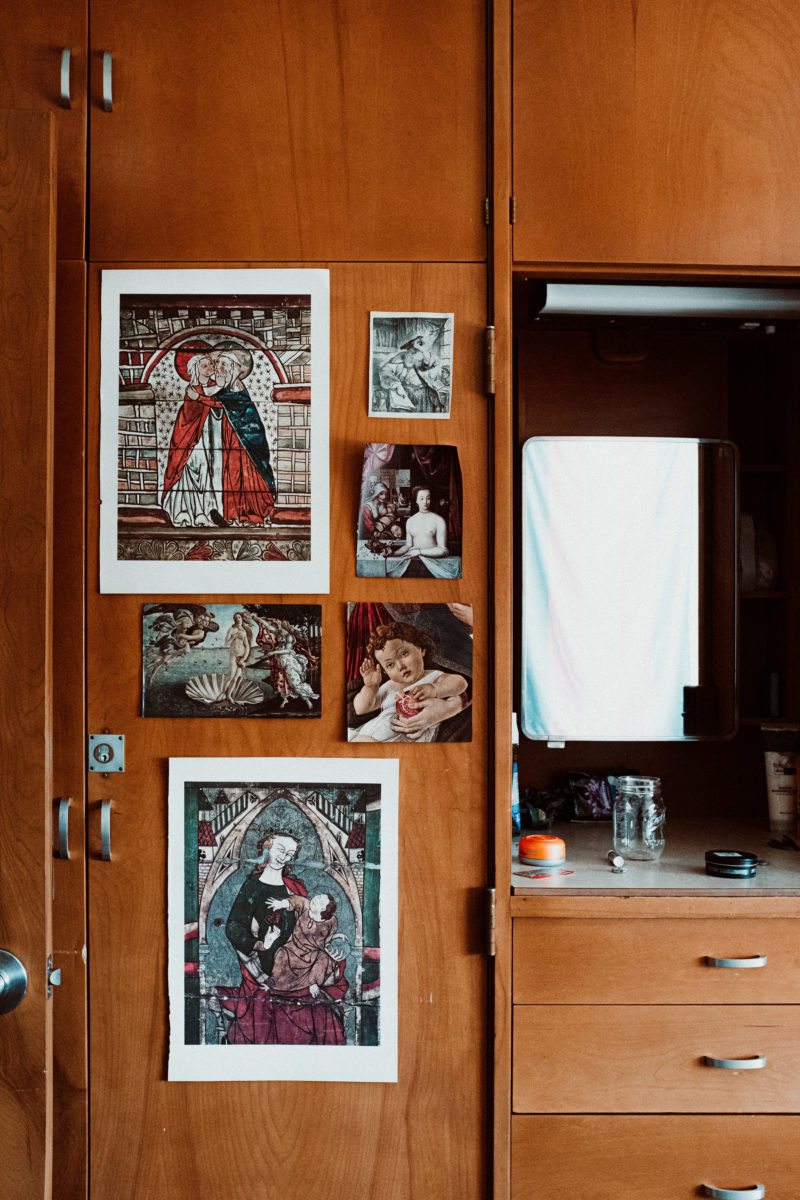 Several prints of art pieces, including the Birth of Venus, on a student's closet door. To the right is a mirror reflecting a white wall.