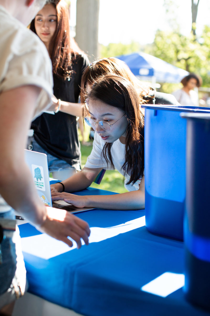 A student leans over a computer to check out a recycling bin at the Orientation welcome tent.