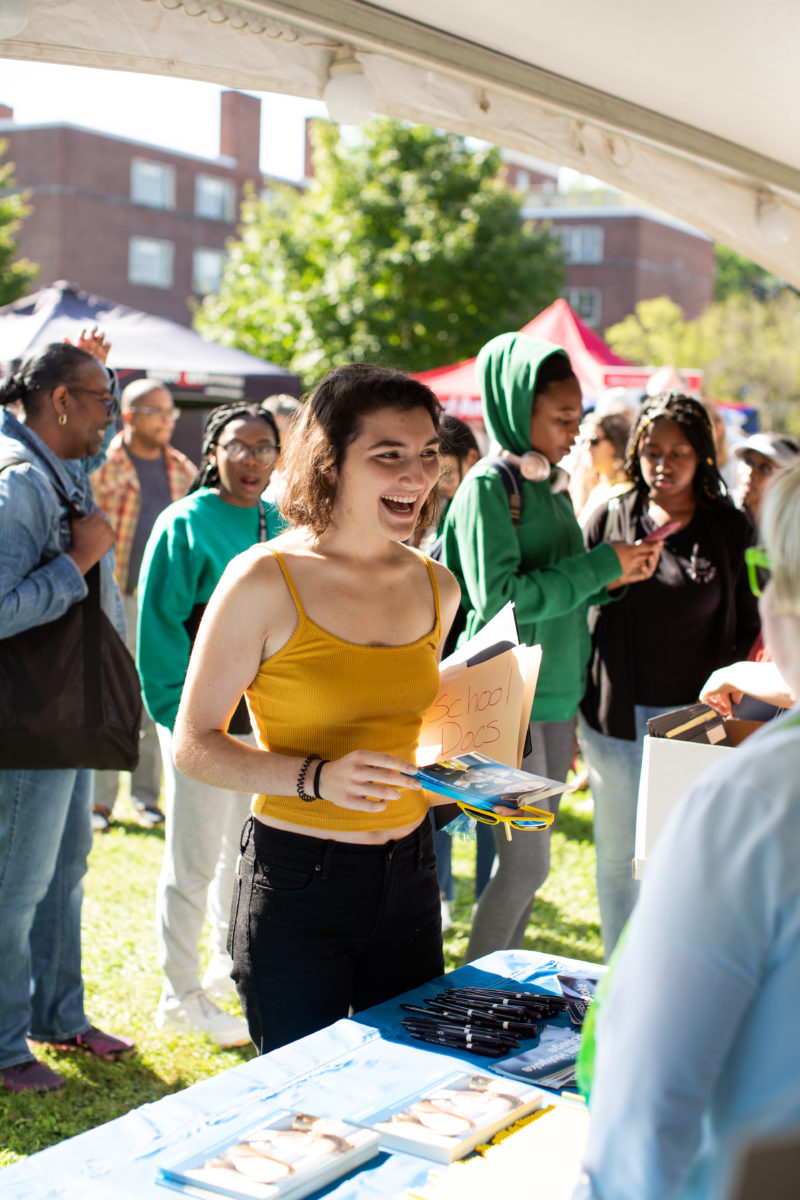 A student in a yellow tank top and black jeans smiles while speaking to people tabling at the Orientation welcome tent. There are people behind them walking to other tents and tables.