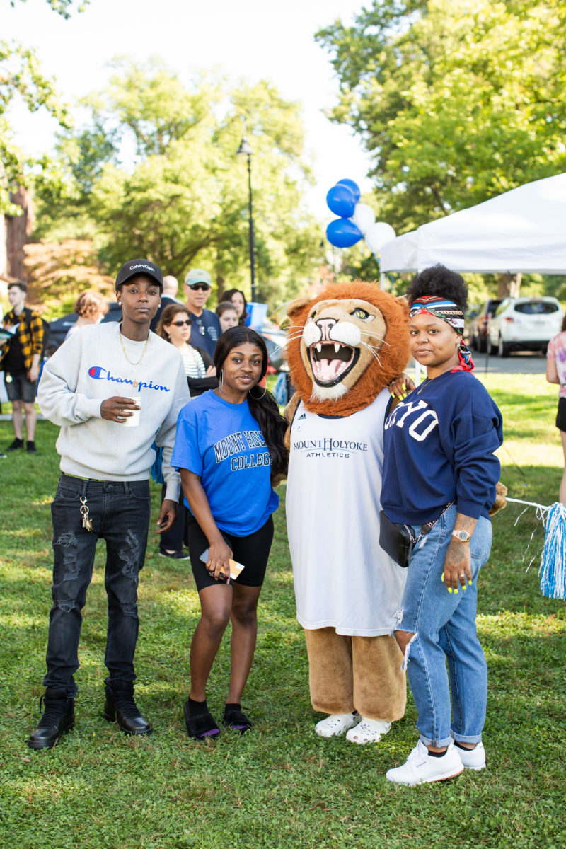 A student and family poses with Paws, the lion mascot, by the Orientation welcome tent.