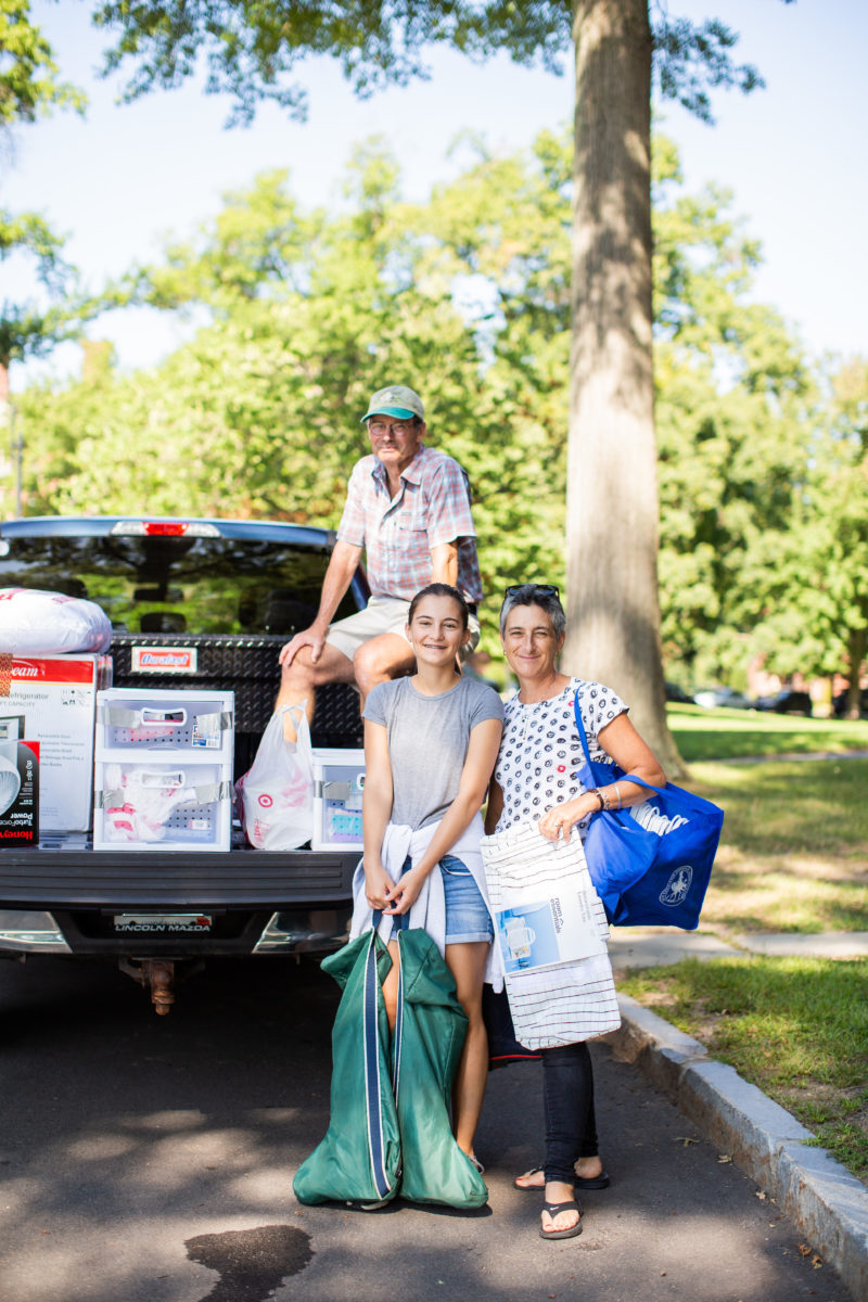 A student smiles with their parents in front of a truck bed loaded with dorm supplies.