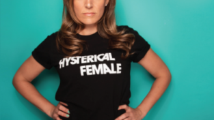 "Jess Inserra '98 posing in front of a teal background. She stares straight into the camera with her hands on her hips and her shirt reads ""hysterical female."""